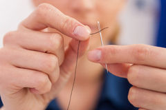 thread-needle-close-up-woman-pulling-40244962