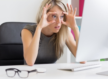Tired woman barely keeps her eyes open in front of computer