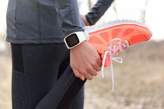 running-stretching-runner-wearing-smartwatch-closeup-shoes-woman-leg-as-warm-up-run-sport-54817824